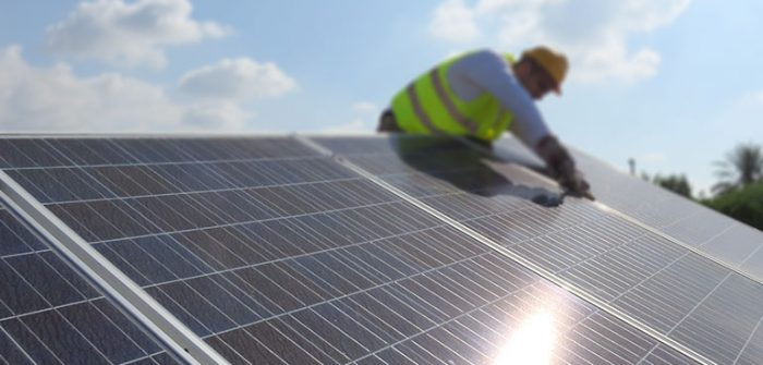 Image of person installing solar cells on a roof